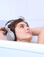 Frau mit Kopfhörer entspannt in Bad