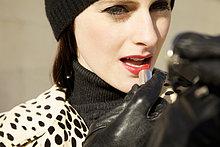 Nahaufnahme einer jungen Frau Anwendung roten Lippenstift