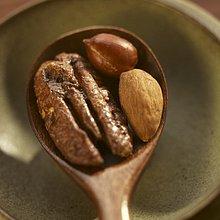 Salzpecannuss, -mandel und -erdnuss auf Holzlöffel
