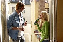 Junges Paar trinkt Bier auf dem Balkon