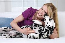 Junge Frau spielt mit Dalmatiner