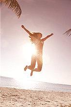 Frau springen in der Luft am Strand