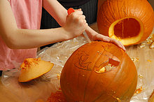 Junges Mädchen, 9 Jahre alt, schneidet ein Gesicht in einen Kürbis, Halloween