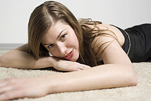 Portrait of a young woman laying on the carpet