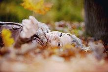 Teenagerin liegend auf Grundstück in Herbst Leaf hält