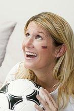 Junge Frau mit deutschen Farben auf ihrem Gesicht hält Fußball