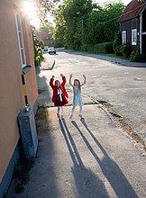 Girls stehen auf Bürgersteig und Erhöhung der Hände