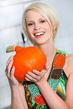 Blonde Frau hält einen Kürbis in der Küche, Portrait