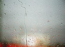 Regen Tröpfchen auf Fenster, roter Bus hinter