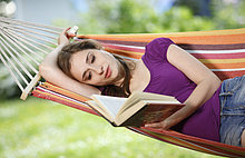 Junge Frau liest ein Buch in einer Hängematte