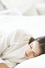 Schönes Mädchen schläft auf weiße Bettwäsche