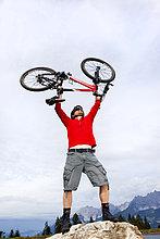 Mann mit Mountainbike auf einer Felsspitze