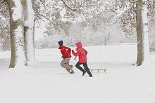 Jungen und Mädchen ausgeführt durch Ziehen Schlitten Schnee
