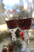 Zwei Gläser Rotwein und Zweig mit Früchten