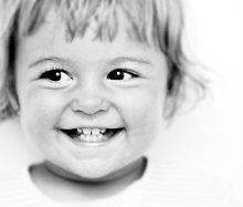 schwarz - weiß - Portrait von kleinem Mädchen mit dunklen Augen - zeigt beim Lachen ihre Milchzähne