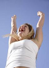 Young Woman with Arms raised an blauer Himmel, Ansicht von unten jubeln