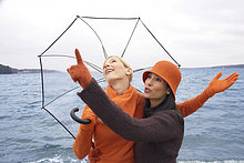 Zwei junge Frauen mit Regenschirm am Meer