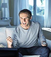 Begeisterter Mann schaut fernsehen und jubelt