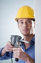 Junger Mann mit Bauhelm benutzt eine Bohrmaschine
