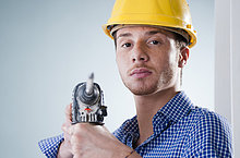 Junger Mann mit Bauhelm benutzt eine Bohrmaschine, Portrait