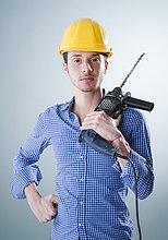 Junger Mann mit Bauhelm hält eine Bohrmaschine