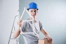 Junger Mann mit Bauhelm hält einen Ziegelstein und einen Zollstock in Form eines Modellhauses