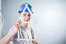 Junger Mann mit Bauhelm hält einen Zollstock in Form eines Modellhauses