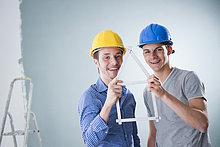 Zwei fröhliche junge Männer mit Bauhelmen halten einen Zollstock in Form eines Hauses