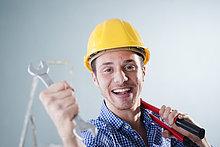 Junger Mann mit Bauhelm hält einen Schraubenschlüssel, Portrait