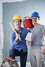 Zwei junge Männer mit Bauhelmen halten Werkzeuge