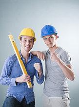 Zwei junge Männer mit Bauhelmen zeigen ihre Muskeln
