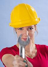 Junge Frau mit Bauhelm hält einen Schraubenschlüssel