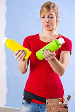 Junge Frau steht mit Fardosen vor einer Wand