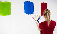 Junge Frau steht mit Farbmustern vor einer Wand