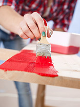 Junge Frau streicht ein Holzbrett