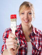 Junge Frau hält einen Pinsel