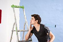 Junger Mann schaut auf eine frisch gestrichene Wand