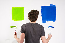 Junger Mann streicht eine Wand