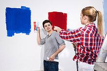 Junges Paar streicht eine Wand
