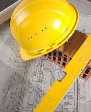 Wasserwaage, Ziegelstein, Bauhelm und Bauplan