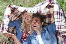 Happy Couple Holding Decke overhead im sonnigen Feld