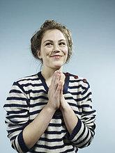 Eine junge Frau mit ihren Händen zusammen mit einem Blick der aufgeregt Hoffnung