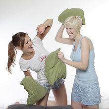 Zwei ausgelassene junge Frauen machen eine Kissenschlacht