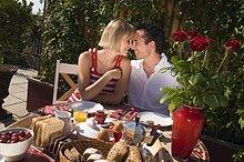 Junges Paar frühstückt im Freien