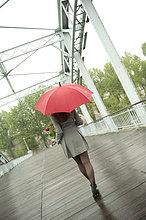 Europäer ,Frau ,gehen ,Regenschirm, Schirm ,Regen ,rot