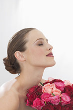 Nahaufnahme einer Frau die mit geschlossenen Augen einen Strauß Rosen hält