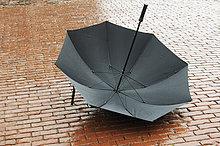Kopfsteinpflaster ,liegend, liegen, liegt, liegendes, liegender, liegende, daliegen ,Regenschirm, Schirm ,nass ,offen