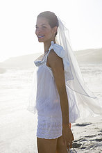 Junge Frau schaut den Wellen zu, Stein am Strand