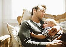 Vater und Kleinkind machen ein Nickerchen auf dem Sofa