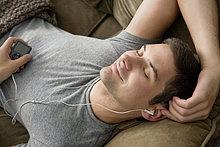Mann,zuhören,Couch,Kopfhörer,dösen